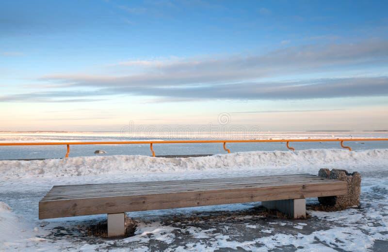 Banco de madera delante del mar del invierno foto de archivo