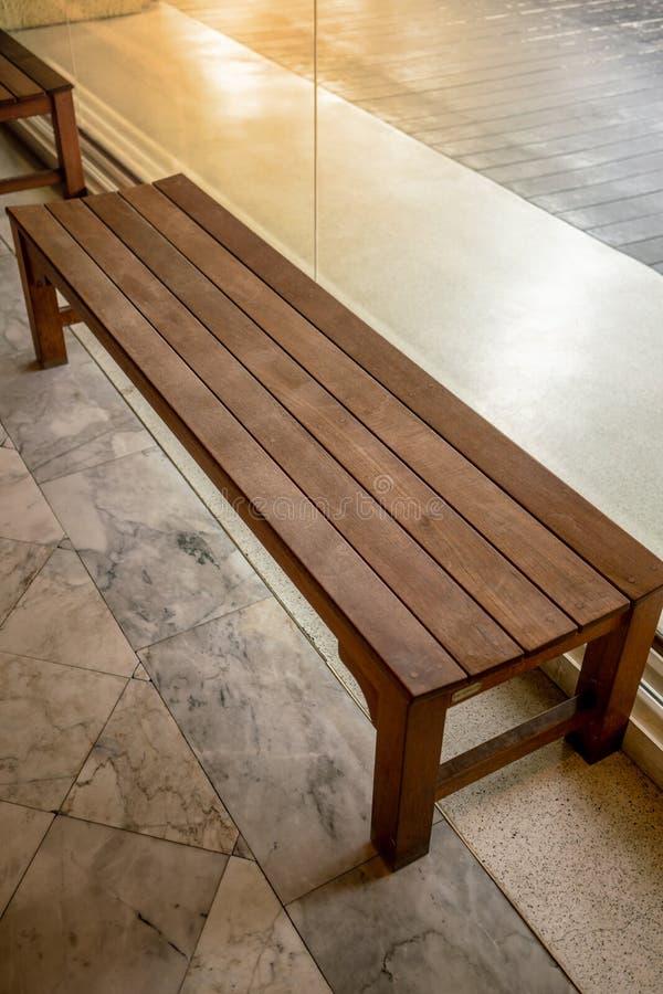 Banco de madera de la silla o de madera dentro de un edificio a lo largo de una calzada imagen de archivo libre de regalías