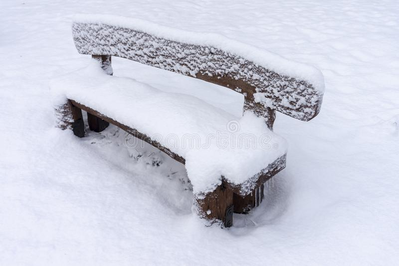 Banco de madera rústico nevado en un parque del invierno foto de archivo libre de regalías