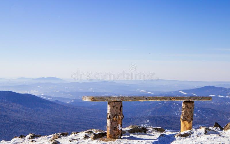 Banco de madera solo al borde de un alto precipicio que pasa por alto la montaña foto de archivo