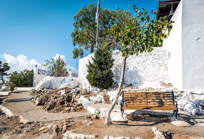 Banco de madera y árbol verde cerca de las paredes de la iglesia de Tsampika en la isla de Rodas, Grecia fotos de archivo libres de regalías