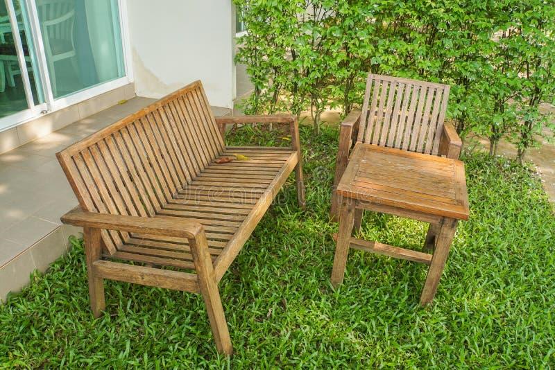 Banco de madera y silla en el césped verde para sentarse fotos de archivo libres de regalías