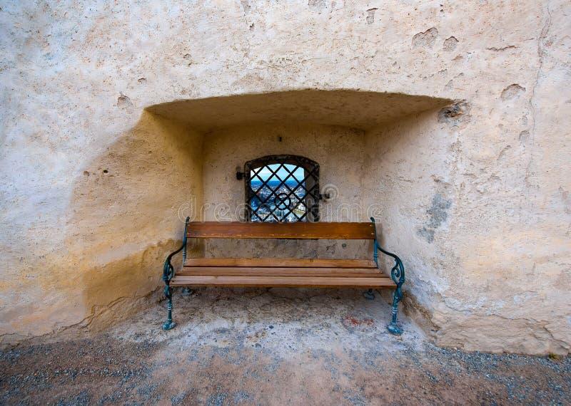 Banco de madera y ventana en la pared de piedra antigua, Salzburg imagen de archivo libre de regalías