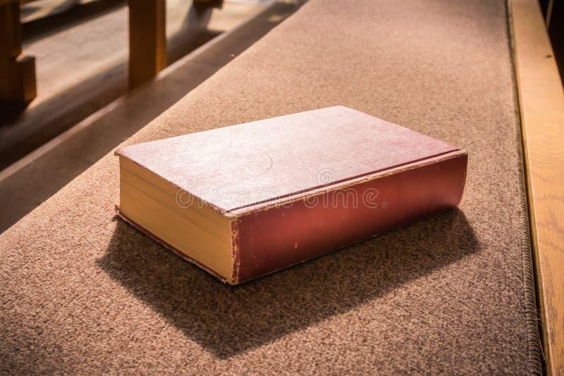 Banco de mentira Woodd C del banco de la iglesia de la vieja de la biblia plantilla vacía roja del libro foto de archivo libre de regalías