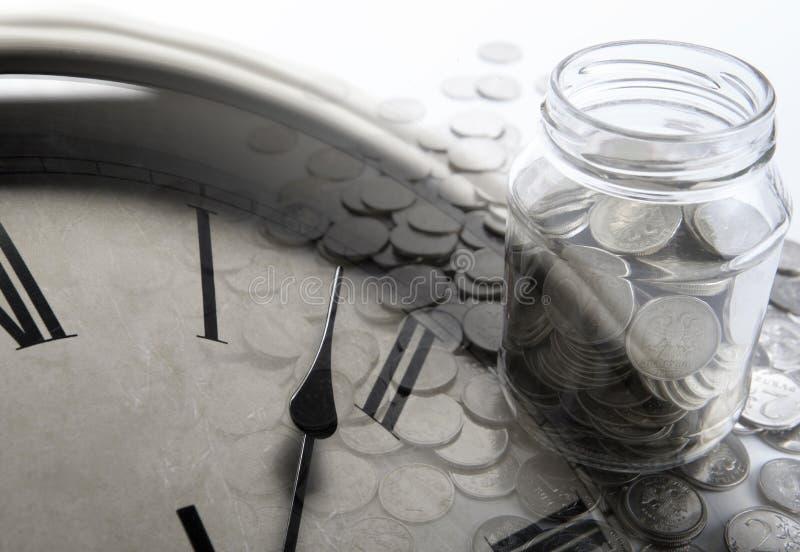 Banco de monedas con los dígitos y la cara de reloj imagen de archivo