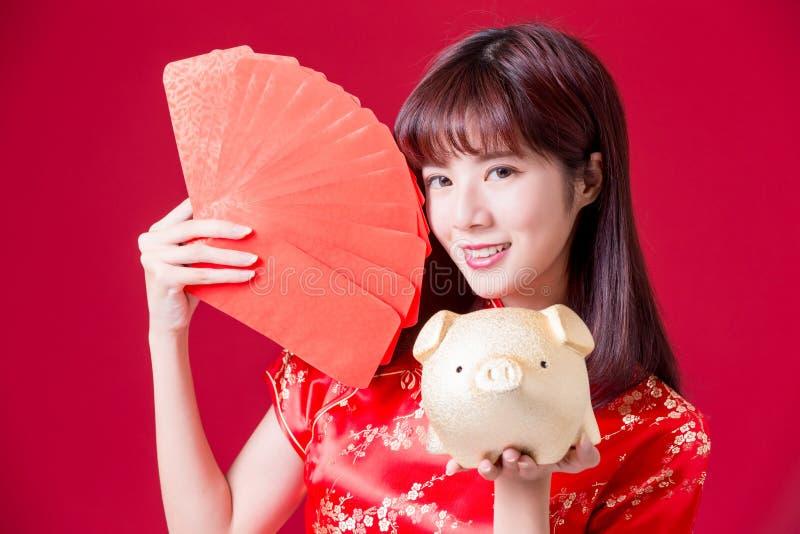 banco de oro del cerdo de la demostración de la mujer y sobre rojo en Año Nuevo chino foto de archivo libre de regalías