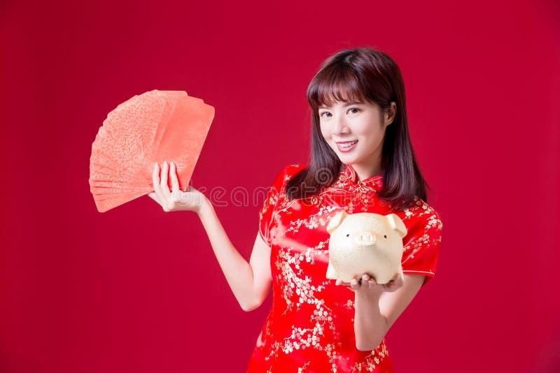 banco de oro del cerdo de la demostración de la mujer y sobre rojo en Año Nuevo chino fotografía de archivo libre de regalías