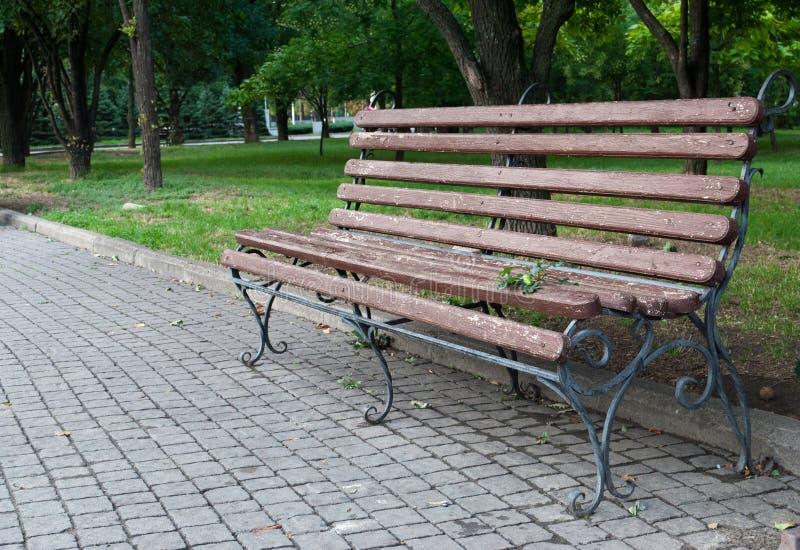 Banco de parque forjado de madera, banco marrón con las piernas forjadas del metal, tejas del pavimento, cuadrado del parque imagen de archivo