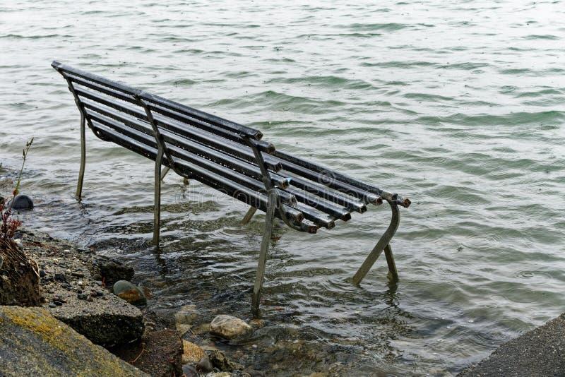 Banco de parque inundado por um nível do mar de aumentação imagens de stock