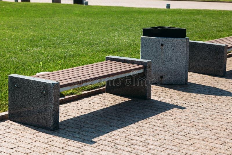 Banco de parque de madera y de piedra y un compartimiento de basura para la basura fotos de archivo libres de regalías