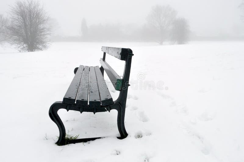 Banco de parque na neve fotografia de stock