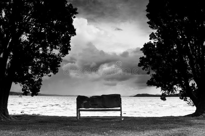 Banco de parque na praia no dia tormentoso fotos de stock
