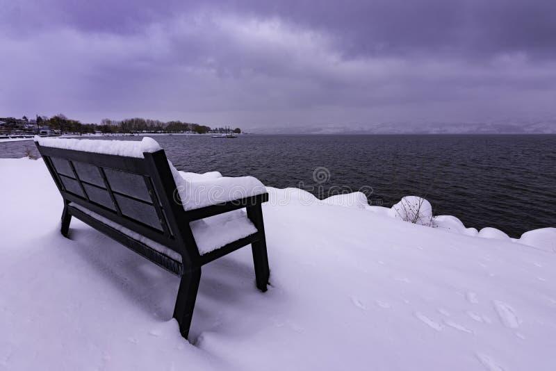 Banco de parque nevado en la Columbia Británica del oeste Canadá de Kelowna del lago Okanagan fotos de archivo libres de regalías
