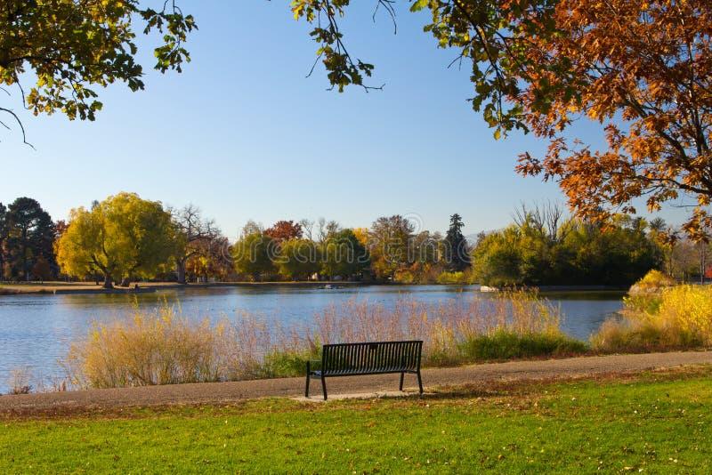 Banco de parque por un lago en caída - Denver imagenes de archivo