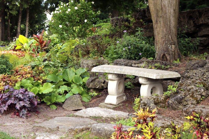 Banco de pedra escondido no jardim imagens de stock