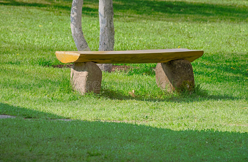 Banco de pedra no gramado do jardim da frente imagem de stock