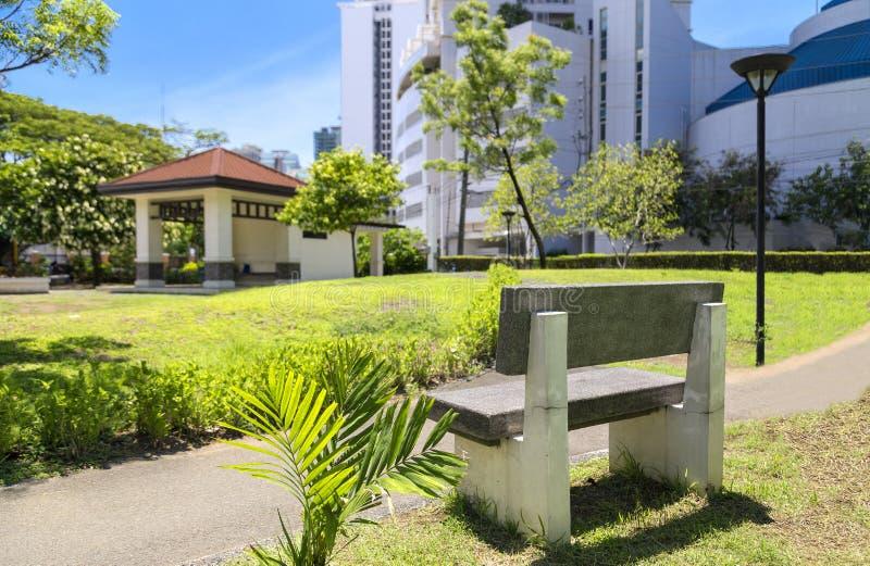 Banco de pedra no parque no centro de Makati, Filipinas fotografia de stock