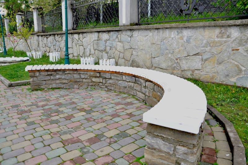 Banco de piedra largo en el parque imagenes de archivo