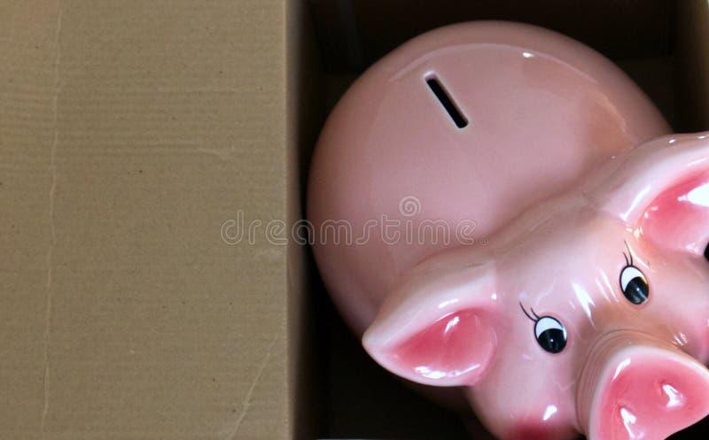 Banco de porquinhos cor-de-rosa com um desenho animado ao lado imagens de stock