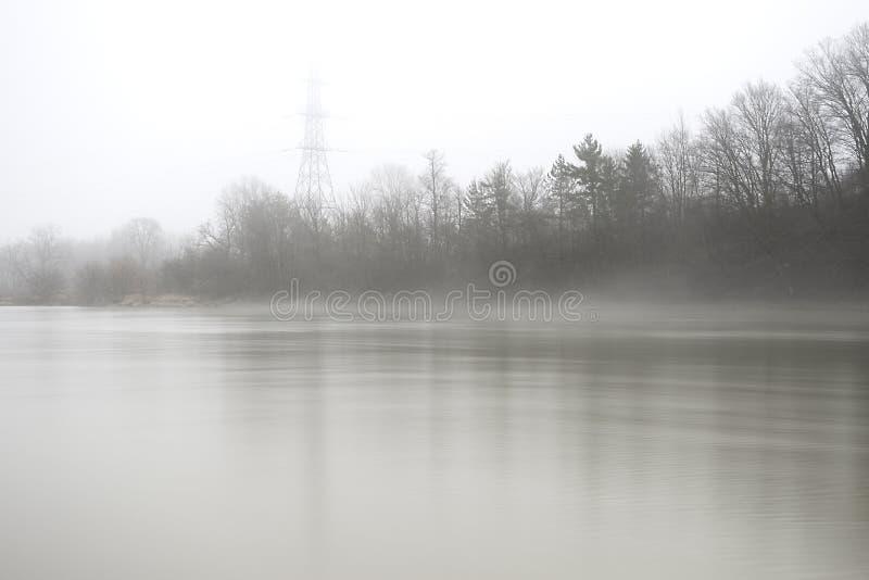 Banco de rio adiantado da mola e torre elétrica que desvanecem-se pelo MI de aumentação fotos de stock royalty free