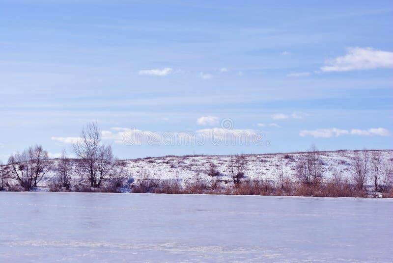 Banco del lago cubierto con el hielo, árboles sin las hojas en la colina, fondo del cielo nublado imagen de archivo