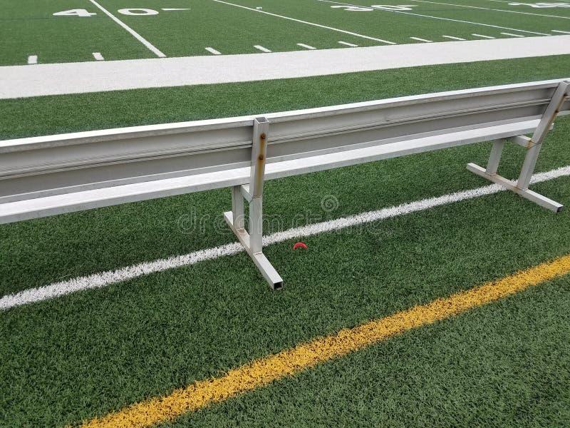 Banco del metallo sul campo di football americano con il boccaglio rosso fotografie stock libere da diritti