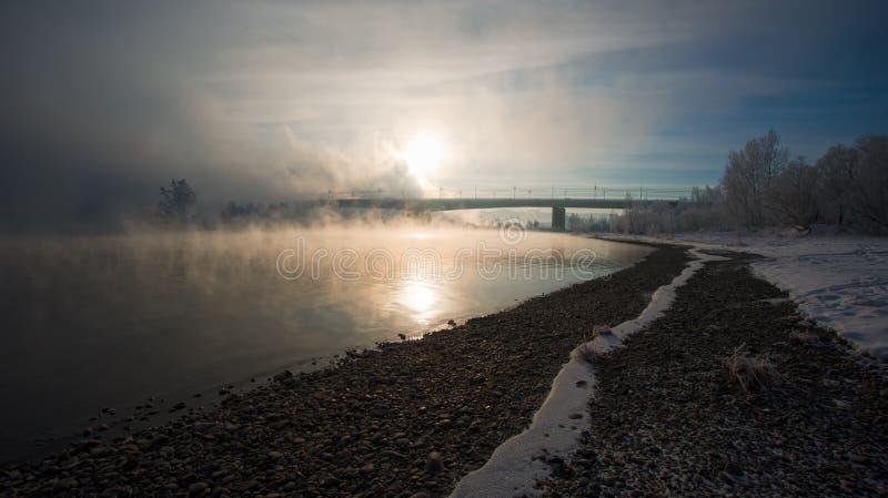 Banco del río y el puente en la niebla foto de archivo
