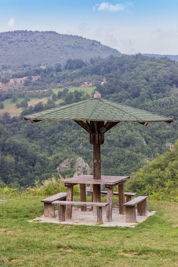 Banco della disposizione dei posti a sedere con la tavola in natura sotto l'ombrello di legno immagine stock
