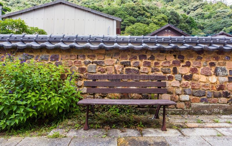 Banco di Brown contro il retro muro di mattoni di stile giapponese fotografia stock