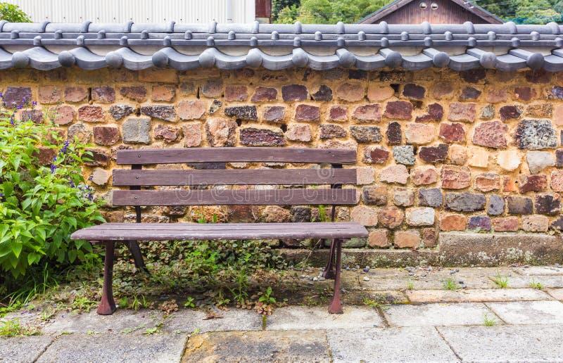 Banco di Brown contro il retro muro di mattoni di stile giapponese immagini stock