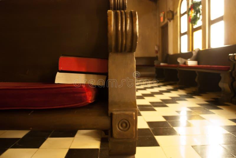 Banco di chiesa della chiesa con la bibbia e l'innario fotografie stock