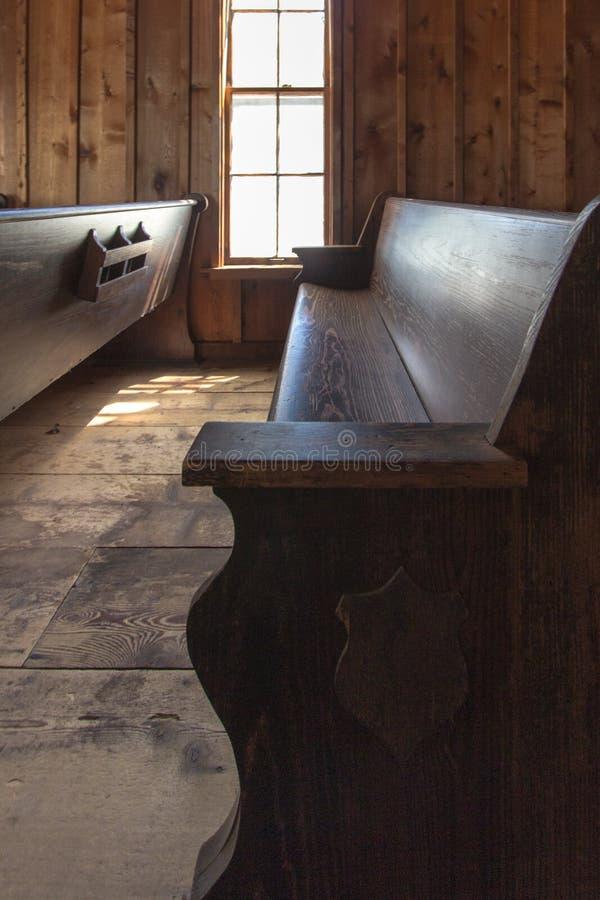 Banco di chiesa di legno vuoto della chiesa nell'orientamento verticale immagine stock libera da diritti