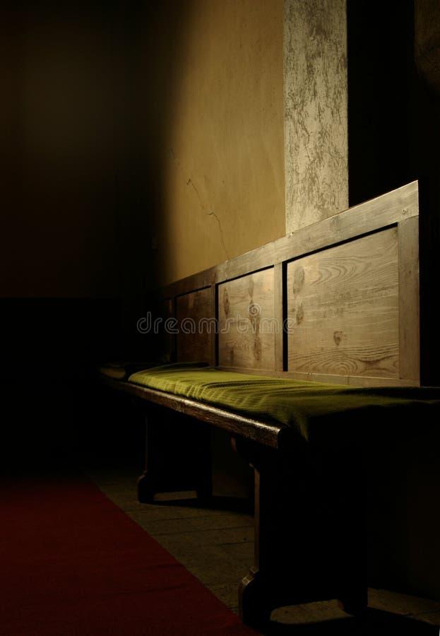 Banco di chiesa nei raggi del sole fotografia stock