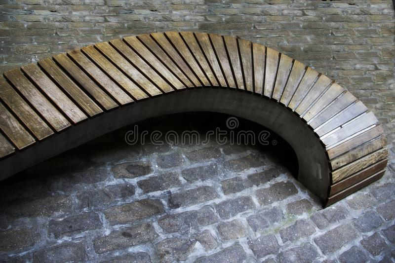 Banco di legno curvo in un parco immagine stock