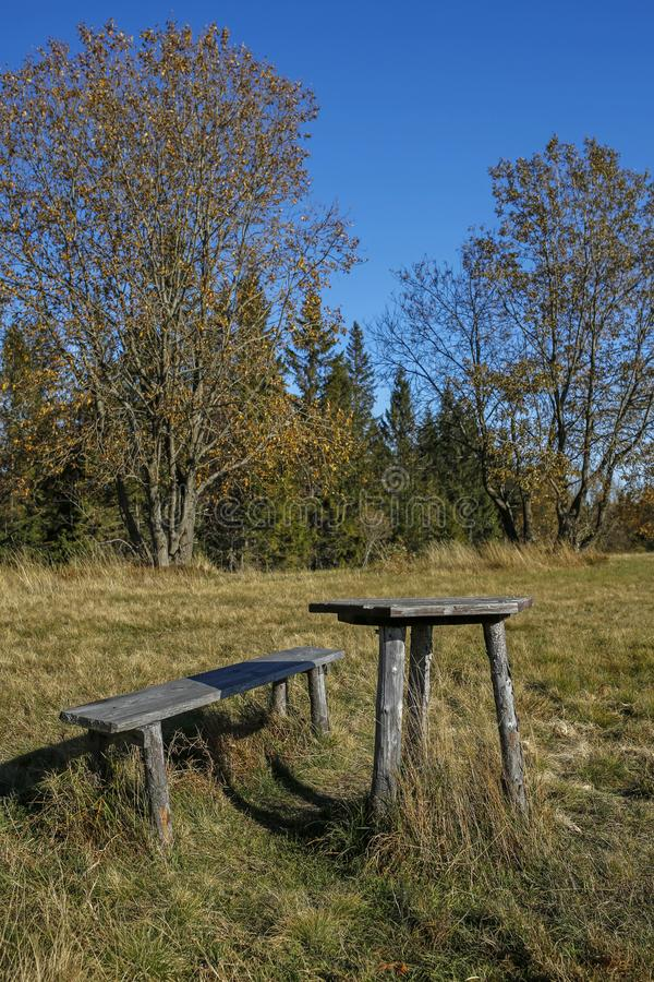 Banco di legno e tavola nel paesaggio della montagna di autunno immagini stock libere da diritti
