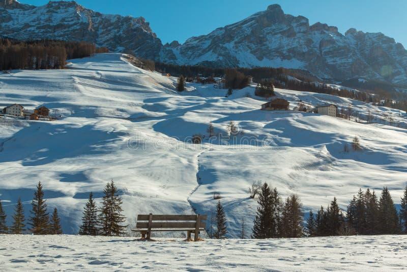 Banco di legno fra neve fresca nell'inverno Sunny Day in italiano Dol immagini stock