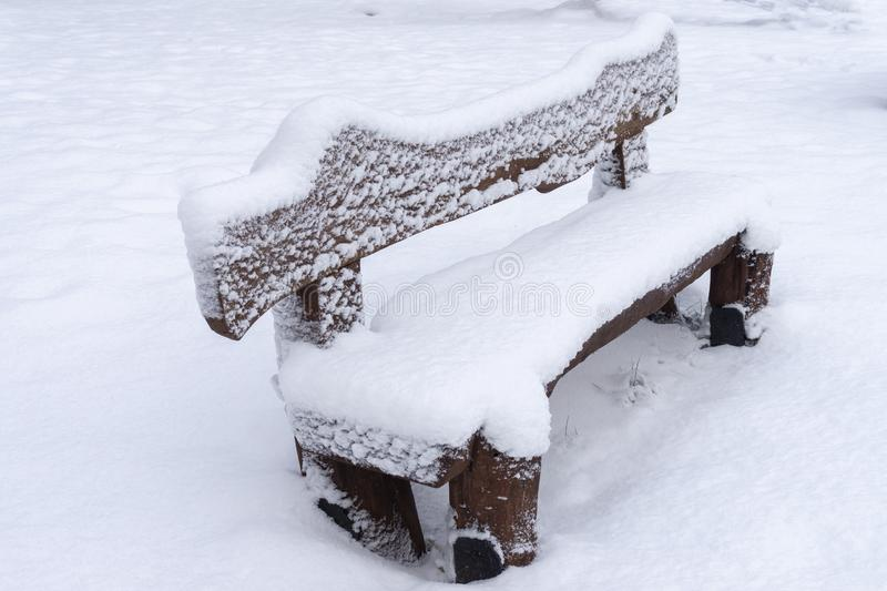 Banco di legno rustico innevato in un parco di inverno fotografia stock libera da diritti