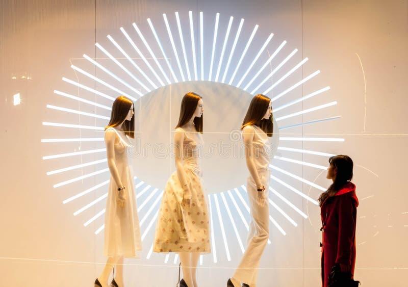 Banco di mostra dei centri commerciali alla finestra della ragazza nel rosso immagine stock