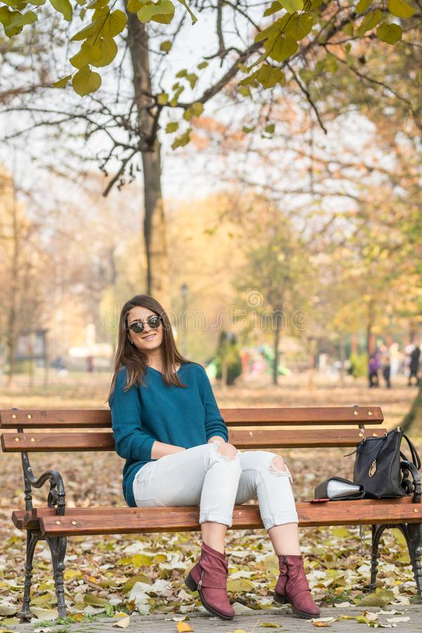 Banco di parco black hat strappato sorridente di seduta di autunno dei jeans del giovane bello adolescente fotografia stock