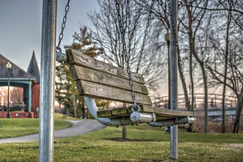 Banco di parco d'oscillazione di legno immagine stock