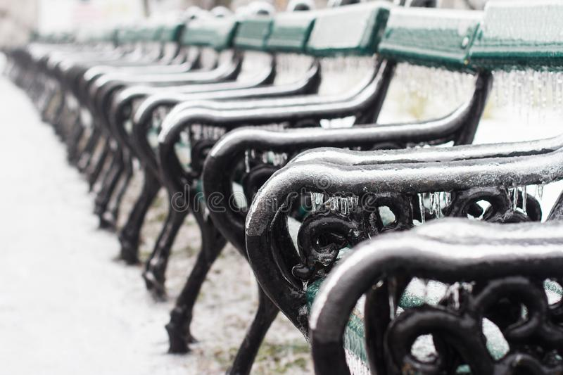 Banco di parco di legno coperto in ghiaccioli di inverno immagini stock