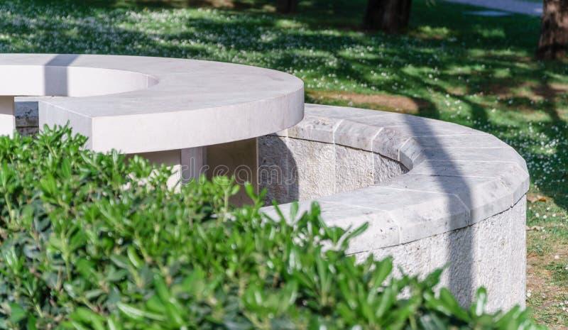 Banco di pietra bianco in un parco di estate fotografie stock