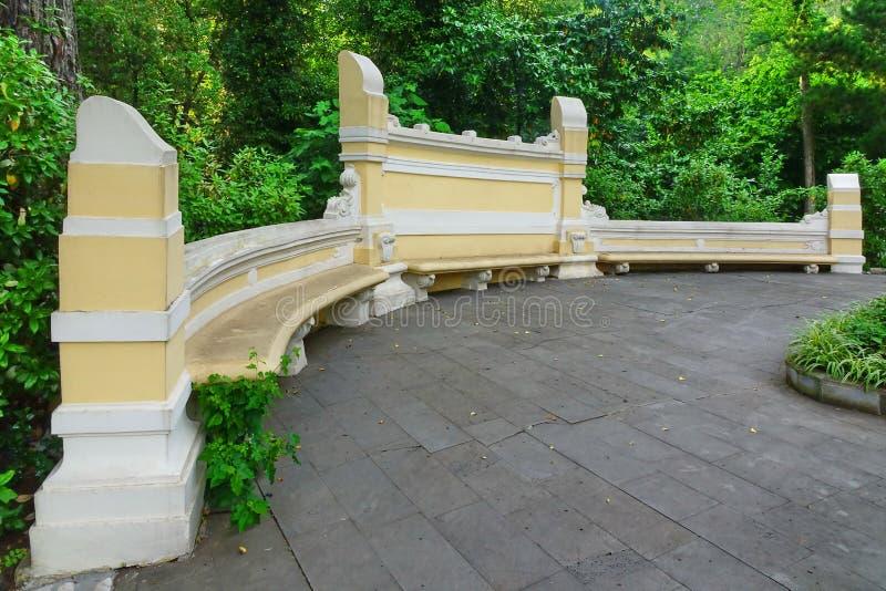 Banco di pietra giallo antico nel giardino botanico pubblico immagini stock libere da diritti