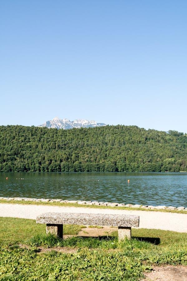Banco di pietra nel lago Levico, Dolomiti, Italia immagini stock libere da diritti