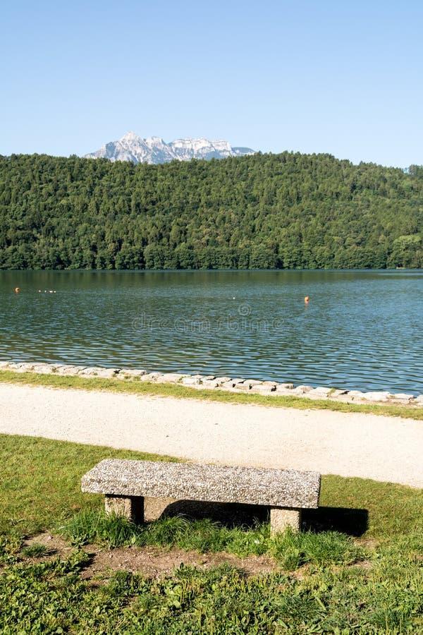 Banco di pietra nel lago Levico, Dolomiti, Italia fotografia stock