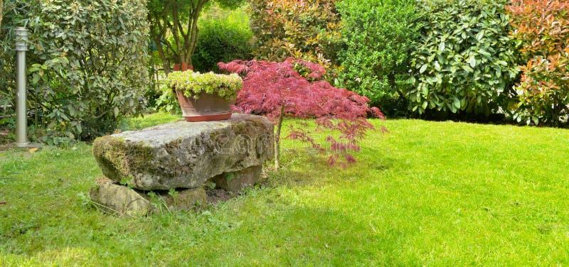 Banco di pietra in un giardino ornamentale fotografia stock