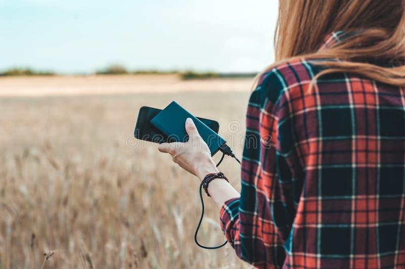 Banco do poder na mão de uma menina, na perspectiva de um campo amarelo fotografia de stock