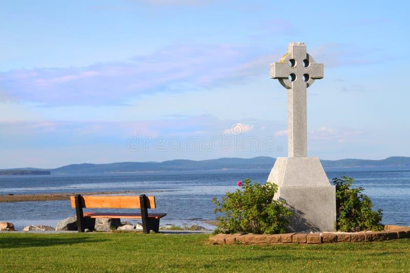 Banco e cruz celta pelo oceano fotografia de stock royalty free