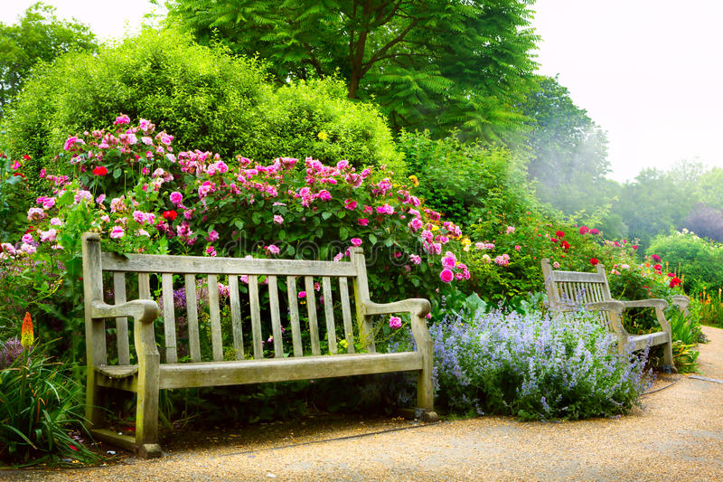 Banco e fiori di arte di mattina in un parco inglese fotografie stock