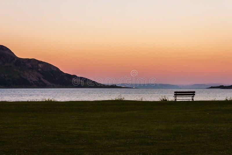 Banco e ilha no por do sol Ilha santamente, Lamlash, Arran, Escócia fotografia de stock